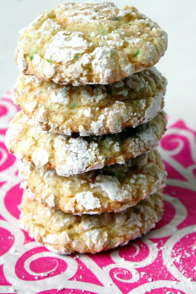 A stack of funfetti crinkle cookies on a pink and white napkins