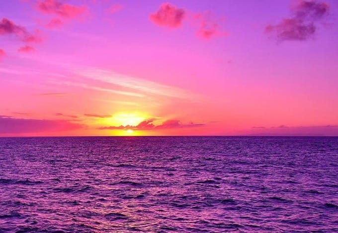 A Kauai Sunset Cruise is never quite the same twice. Here the yellow sun colors the sky pink as it sinks down into the ocean.