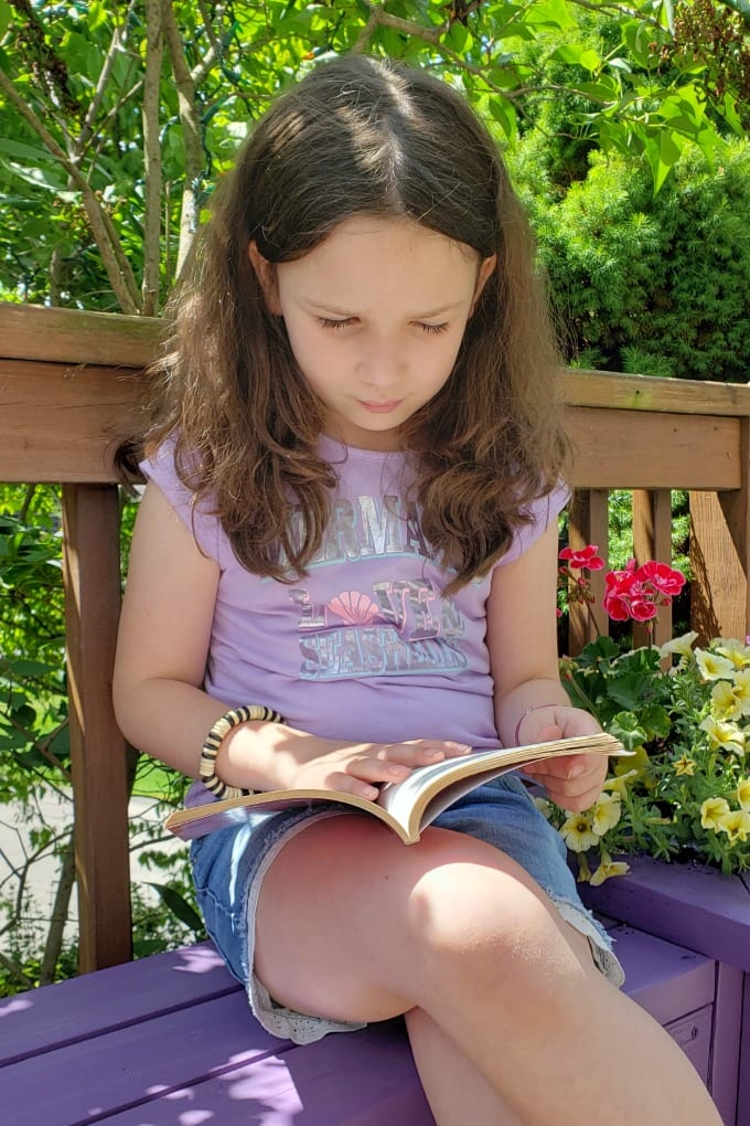 A young girl sits on a a purple Planter Box Bench reading a book.