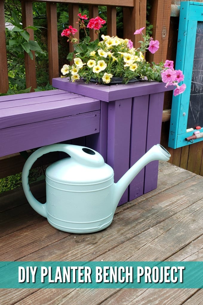 A watering can sits near the base of a purple Outdoor Planter Bench with pink and yellow flowers planted in it.