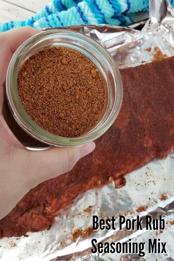 A hand holds small jar of homemade pork seasoning. Uncooked ribs covered with the spice mixture can be seen in the background.