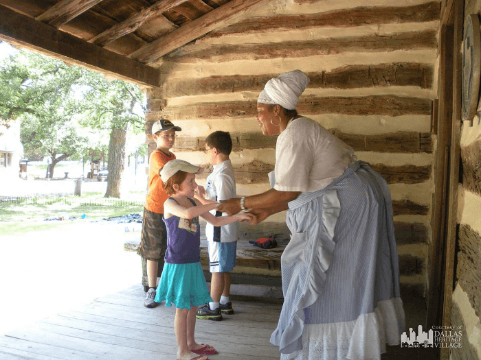 African American Living history Docent with children in a log cabin