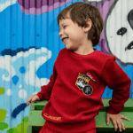 young boy in a red shirt against a graffiti background
