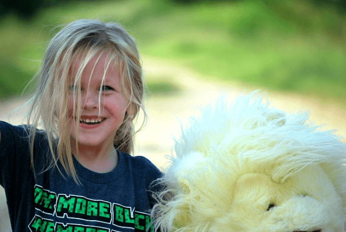 Blonde girl smiling while holding a stuffed animal