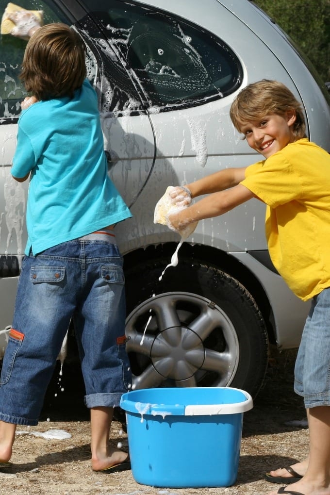 Two kids washing a car