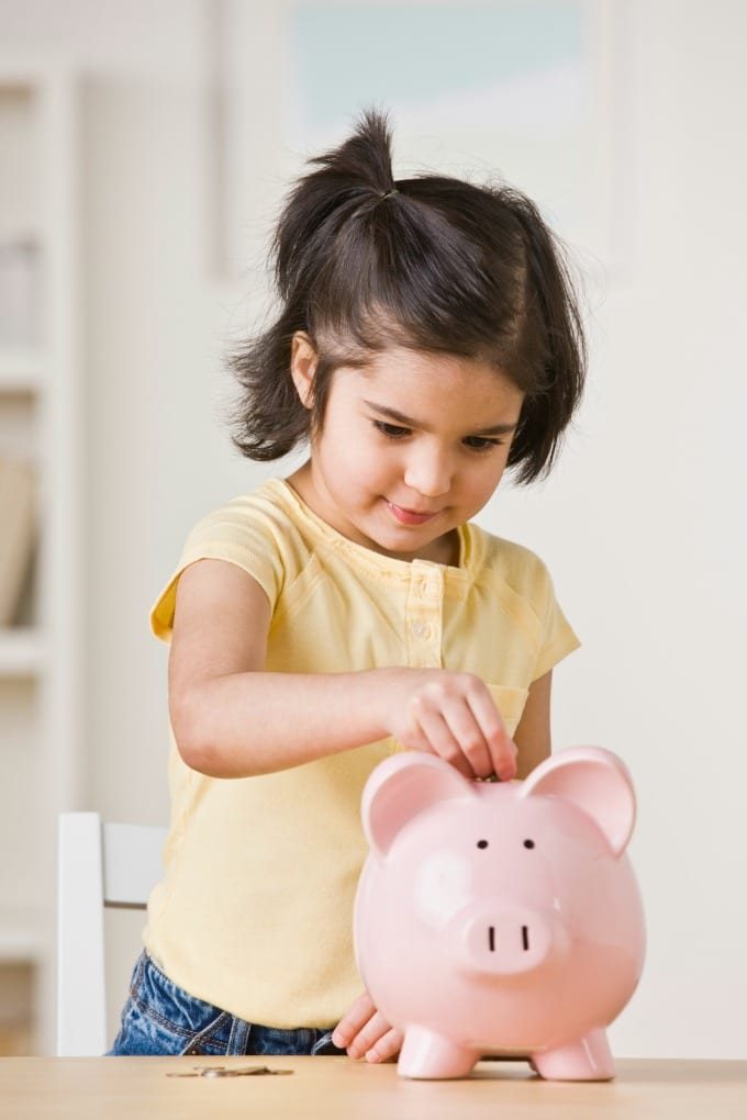 Little girl in a yellow shirt putting coins into a pink piggy bank