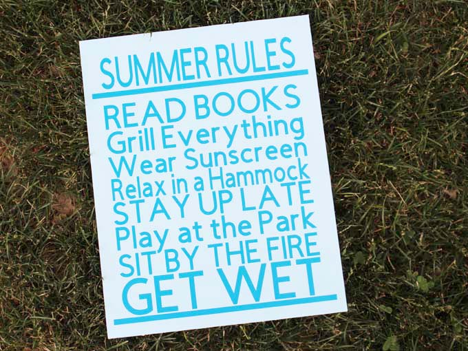 Summer Rules family wood sign sitting on the grass.