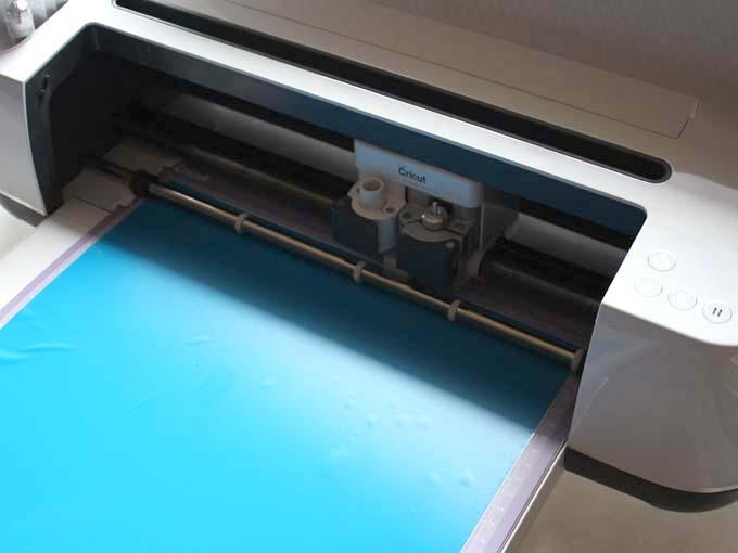 Cricut Maker cutting blue vinyl for Summer subway art sign.