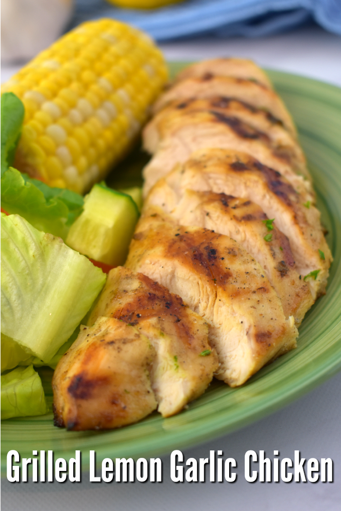 A close up of lemon garlic grilled chicken cut into slices on a green dinner plate next to a garden salad and corn on the cob.