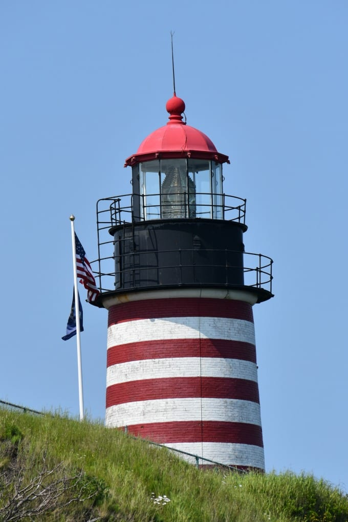 Image of West Quoddy Head Lighthouse next to an American flag and state of Maine flag blowing in the wind.