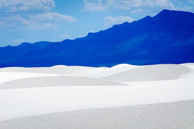 White sand dunes against a dark blue mountain.