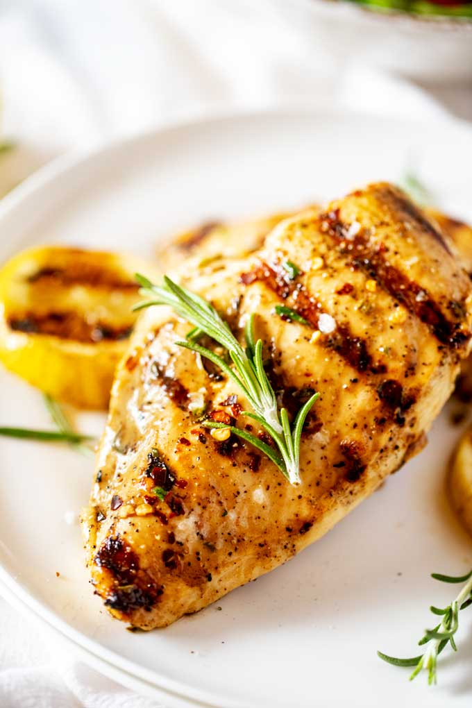 Close up photo of Grilled Lemon Pepper Chicken on a white plate.