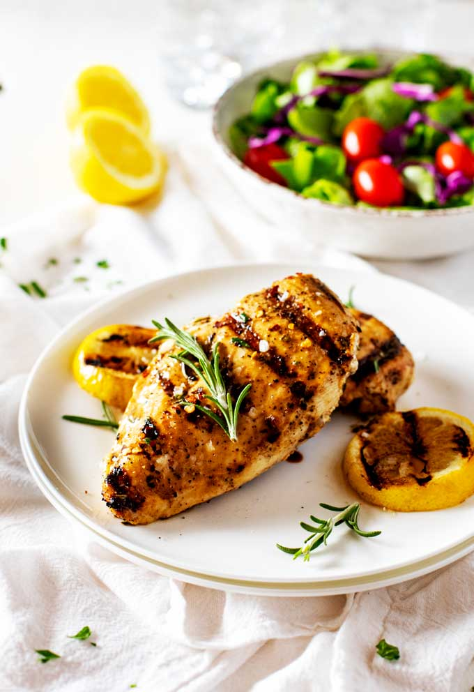 This easy to make Grilled Lemon Pepper Chicken has a tangy marinade that the whole family will love! Perfect for family dinners. #grillingrecipes #GrilledLemonPepperChicken #easyrecipes via @jugglingactmama