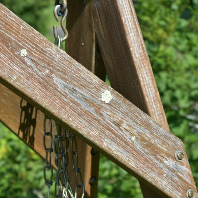 A close up of a shabby outdoor wooden swing.