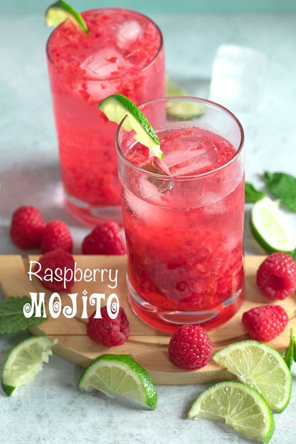 Front view of two glasses filled with raspberry mojito and surrounded by raspberries, lime and mint leaves