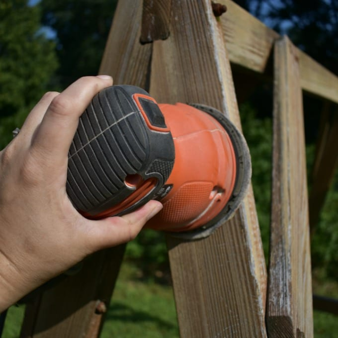 A hand holding an orbital sander working on a shabby outdoor wooden swing.
