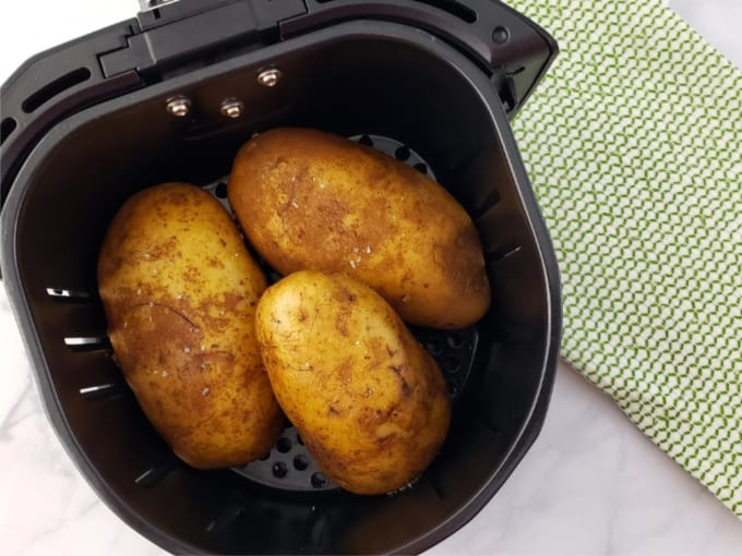 Three oil-rubbed russet potatoes in the basket of an air fryer.