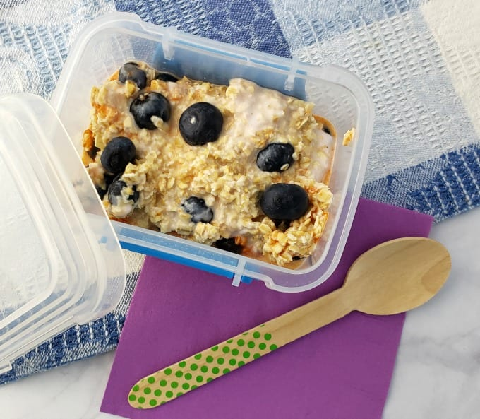 Blueberry Overnight Oats in a small containers on a marble counter with a purple napkin and wooden spoon.