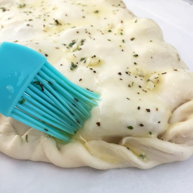 A pastry brush adds melted herbed butter on a calzone dough.
