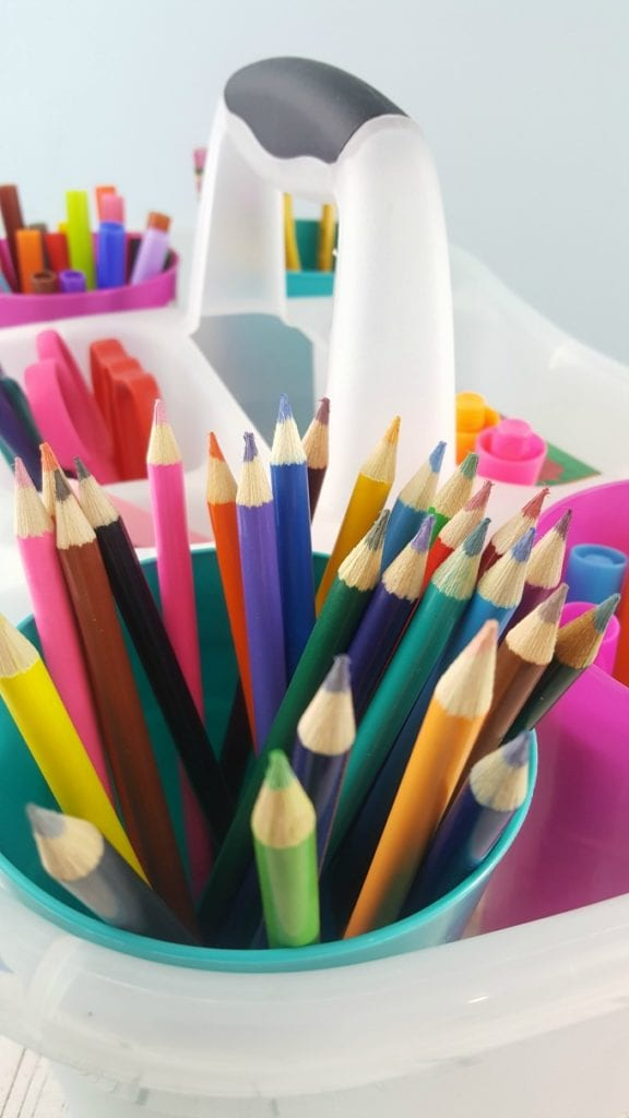 A close up of colored pencils in a clear plastic caddy with other school supplies.