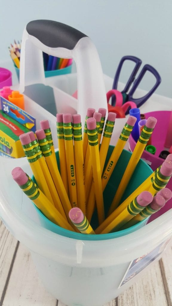 A close up of pencils in a clear plastic caddy with other school supplies.