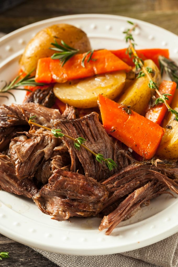 Homemade Italian Beef Roast with potatoes and carrots on a white dinner plate