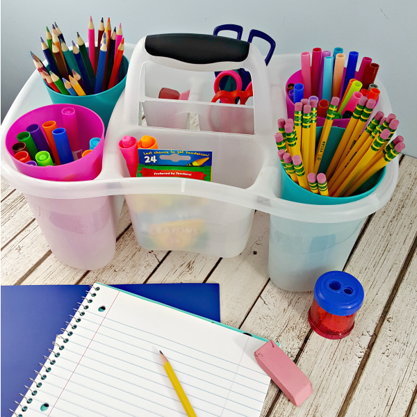 A homework station using a shower caddy with pencils, markers, glue sticks and other school supplies on a wooden table next to a notebook, pencil and eraser.