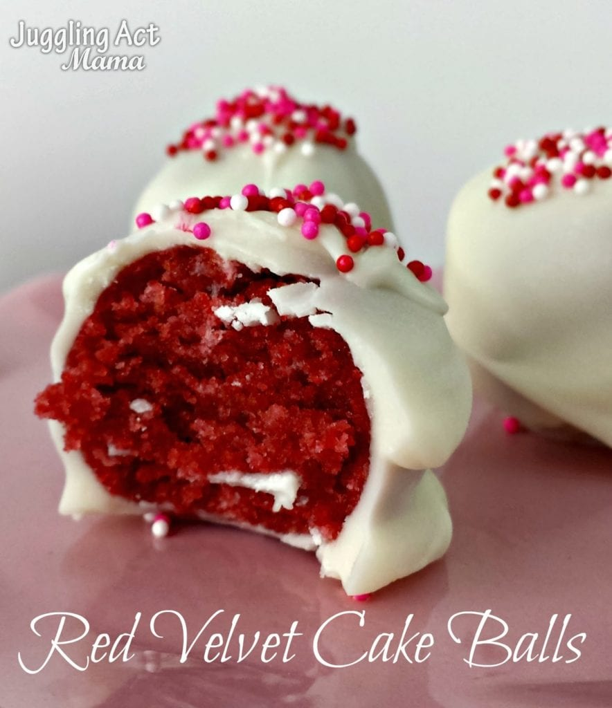 A red Velvet Cake Ball covered with white chocolate sits on a pink plate with a bite taken out of it