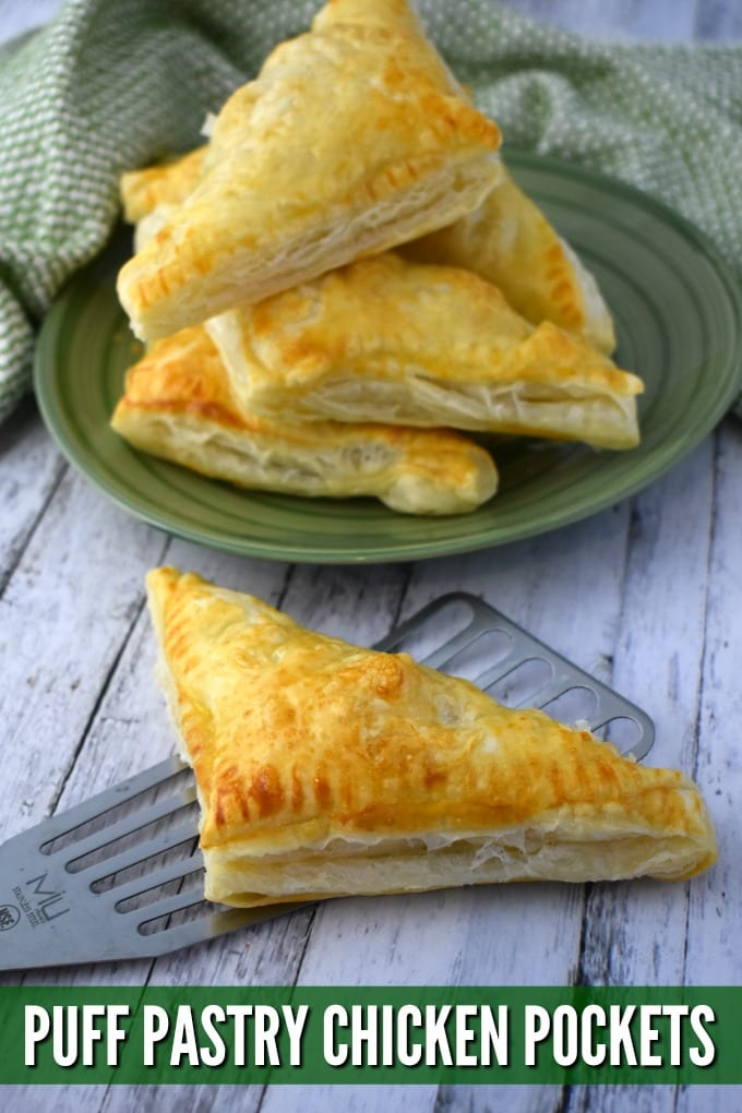 Golden brown Puff Pastry Chicken Pocket rests on a metal spatula at the forefront. A green plate is piled high with more puff pastry chicken.
