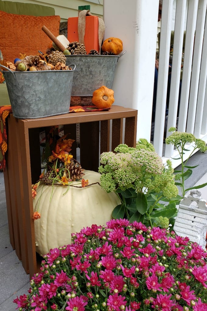 Fall Porch Decorating Ideas - a porch and front door decorated for Fall with colorful mums, pumpkins and other decorations.