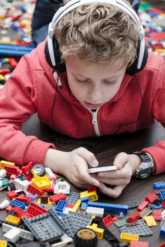boy surrounded by legos wearing headphones and playing with a phone - How to Limit Screen Time