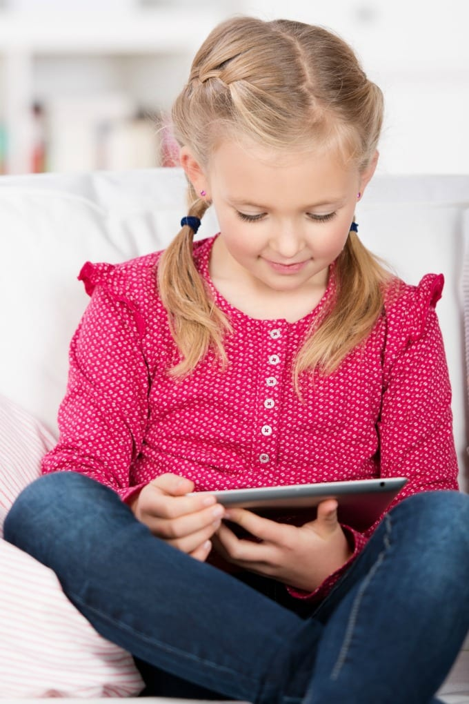 little girl use tablet pc in the house this article will teach you How to Limit Screen Time