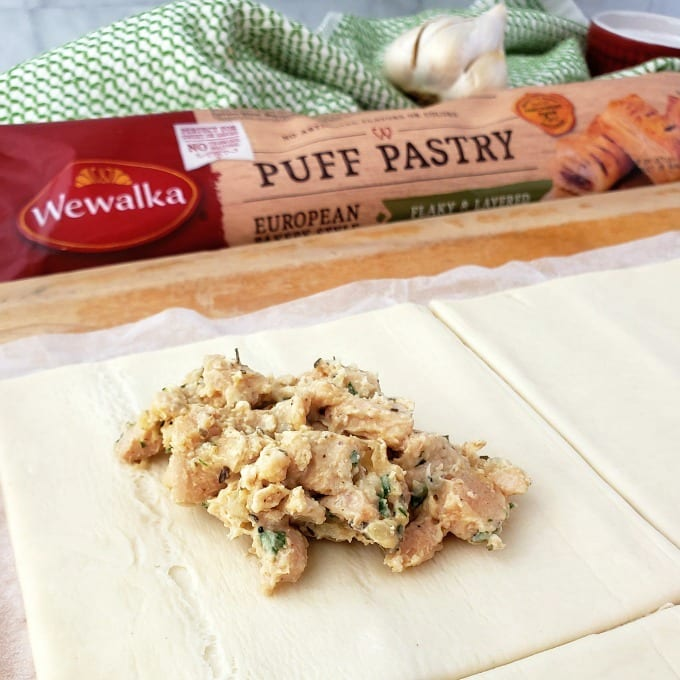 Package of Wewalka Puff Pastry Dough next to a green hand towel. Rolled out dough with chicken filling in the middle.