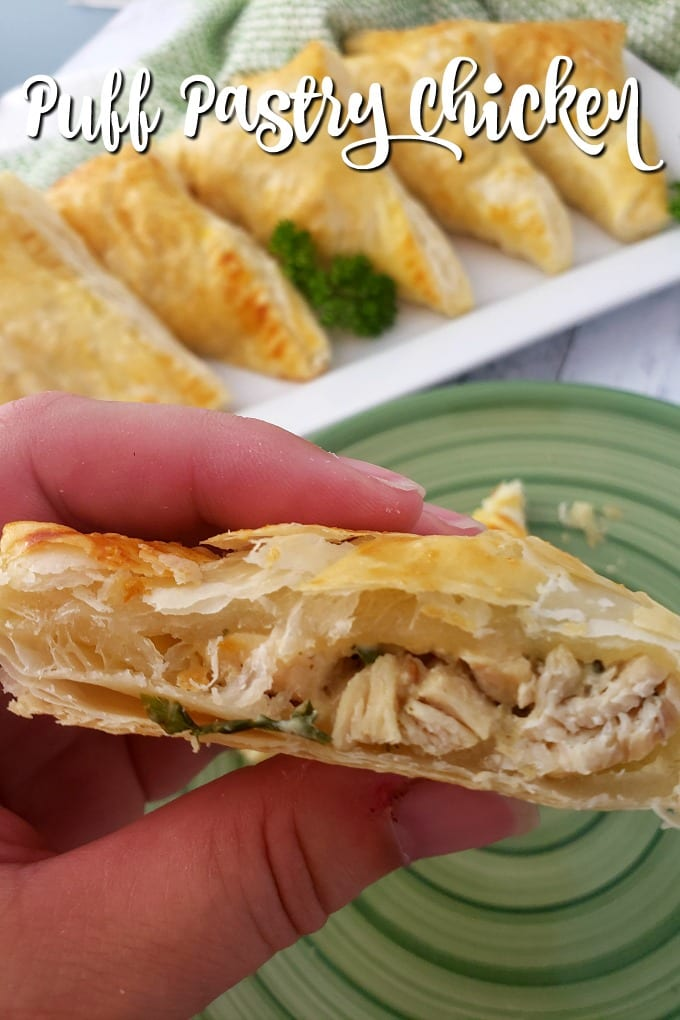 A hand holds a golden brown Puff Pastry Chicken Pocket that has been cut in half. More puff pastry chicken in in the background on a white serving tray.