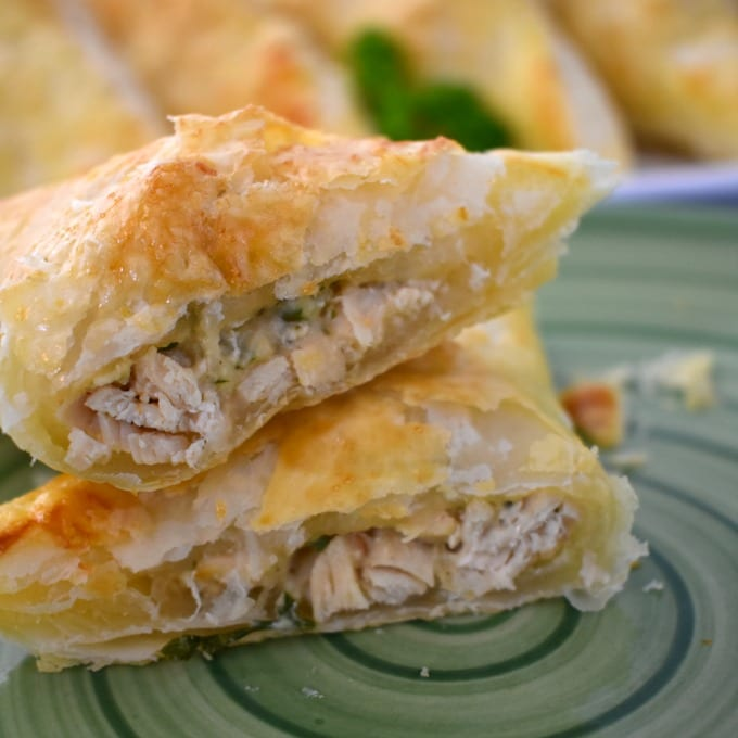 puff pastry stuffed chicken cut and stacked on a green plate