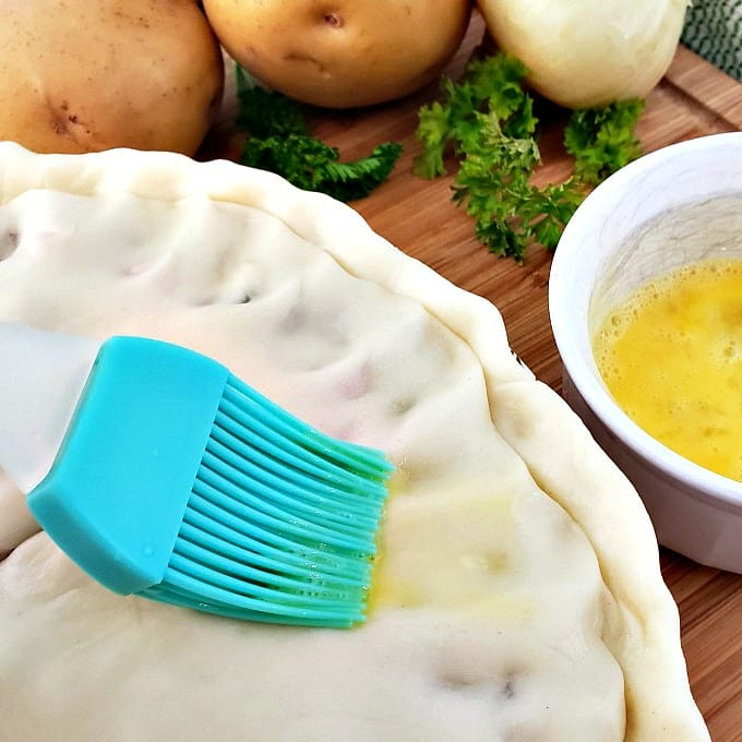 close up of a pastry brush adding an egg wash to a pie crust.