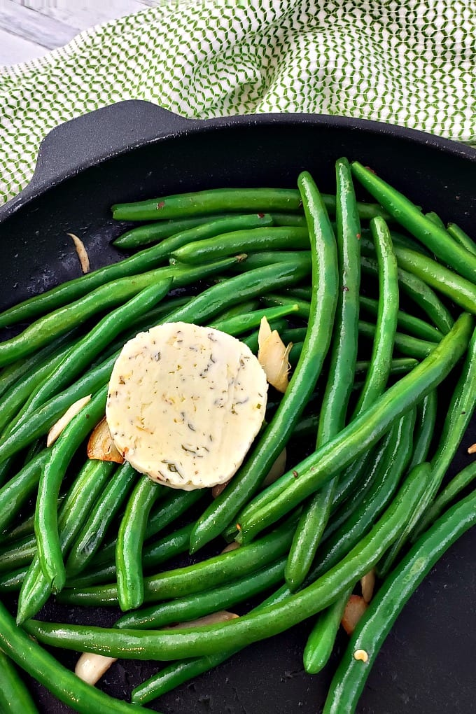 cooked and seasoned green beans in a skillet dish topped with sauteed garlic and compound butter