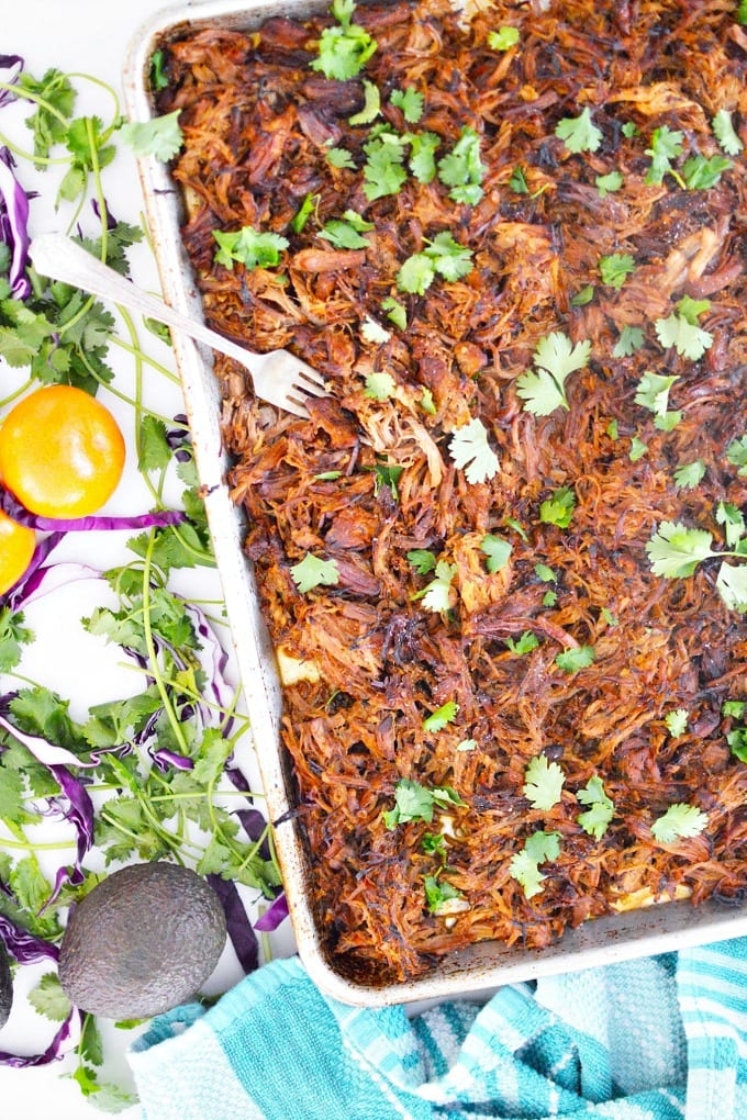 a sheet pan of crispy pork carnitas garnished with cilantro leaves