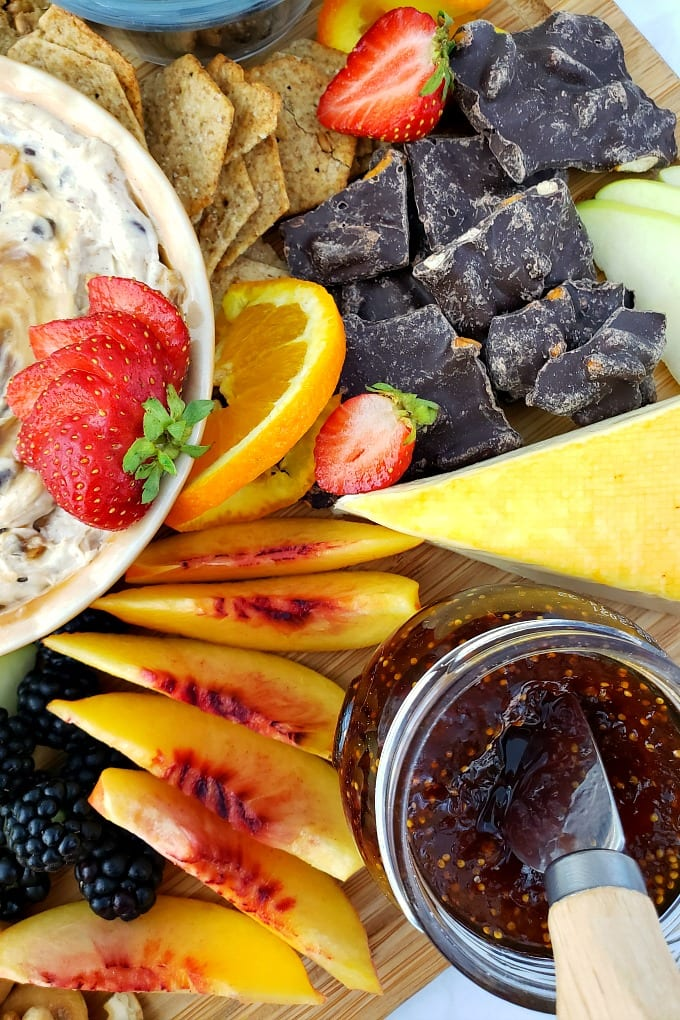 close up of a fruit platter with peaches, fig jam, dark chocolate and other items.