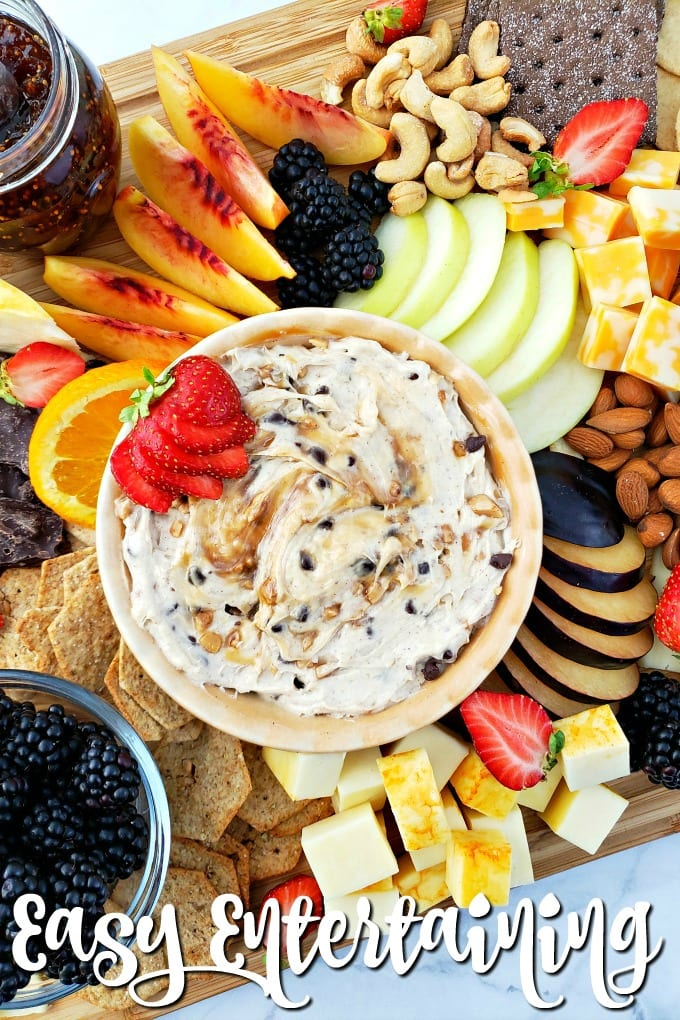 Top down view of a fruit cheese platter with a variety of items to choose from such as sliced fruits and berries, nuts, and cheeses.