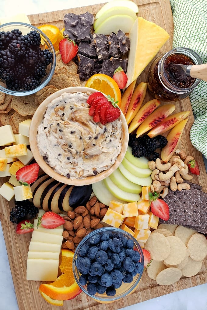 Top down view of a fruit and cheese platter with a variety of items to choose from.