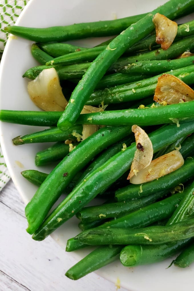 cooked and seasoned green beans in a white dish topped with sauteed garlic and lemon zest.