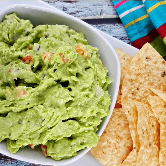 close up of a bowl of guacamole with tomatoes and red onions next to tortilla chips.