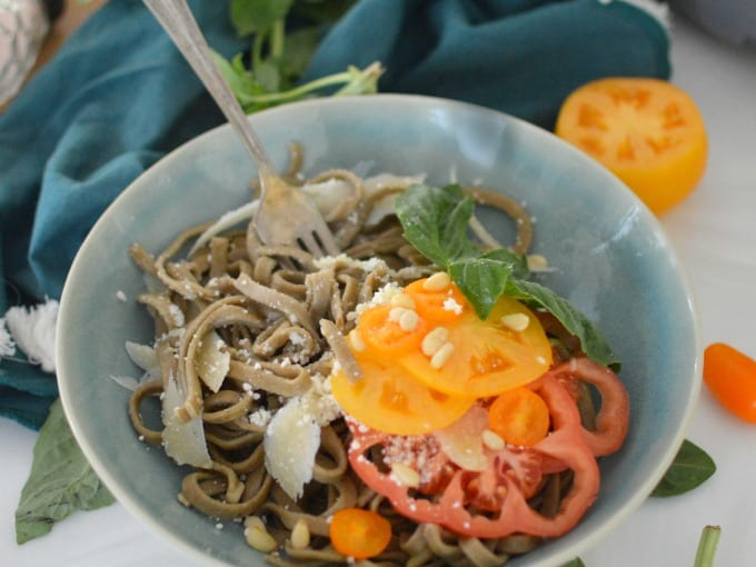 a bowl of cooked homemade spinach pasta with heirloom tomatoes and pine nuts