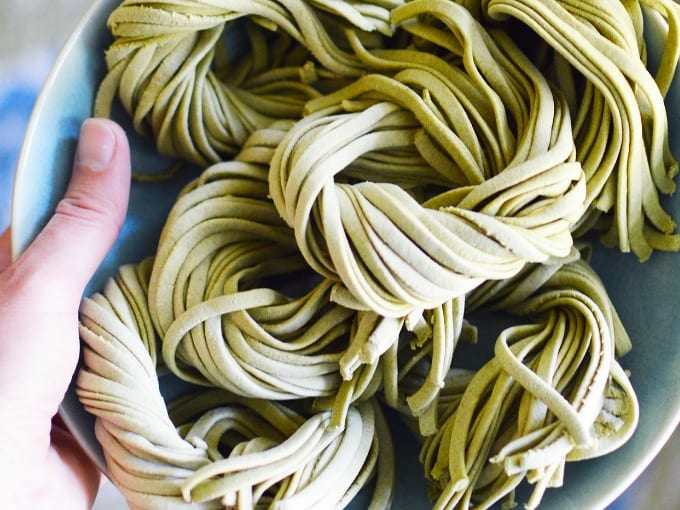 a hand holds swirls of homemade spinach pasta