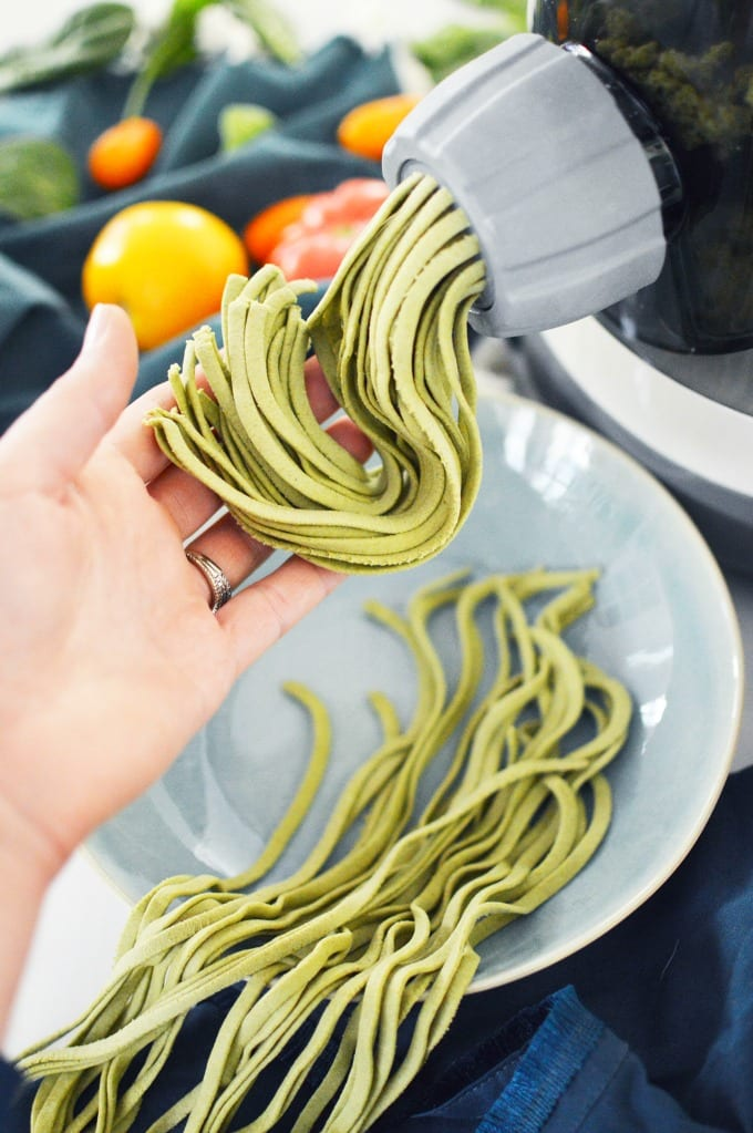 a hand catches the spinach pasta as it is extruded from a pasta maker
