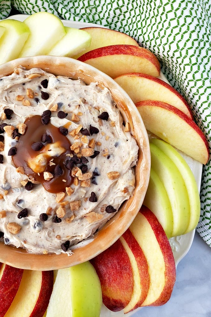 Red and green apple slices are arranged around a bowl of Toffee Apple Dip.