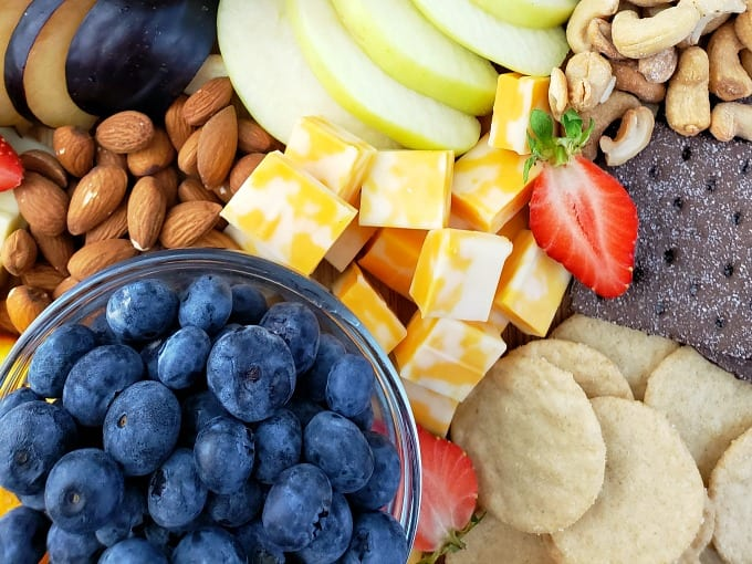close up of a fruit and cheese platter including blueberries, colby jack cheese, crackers and nuts.