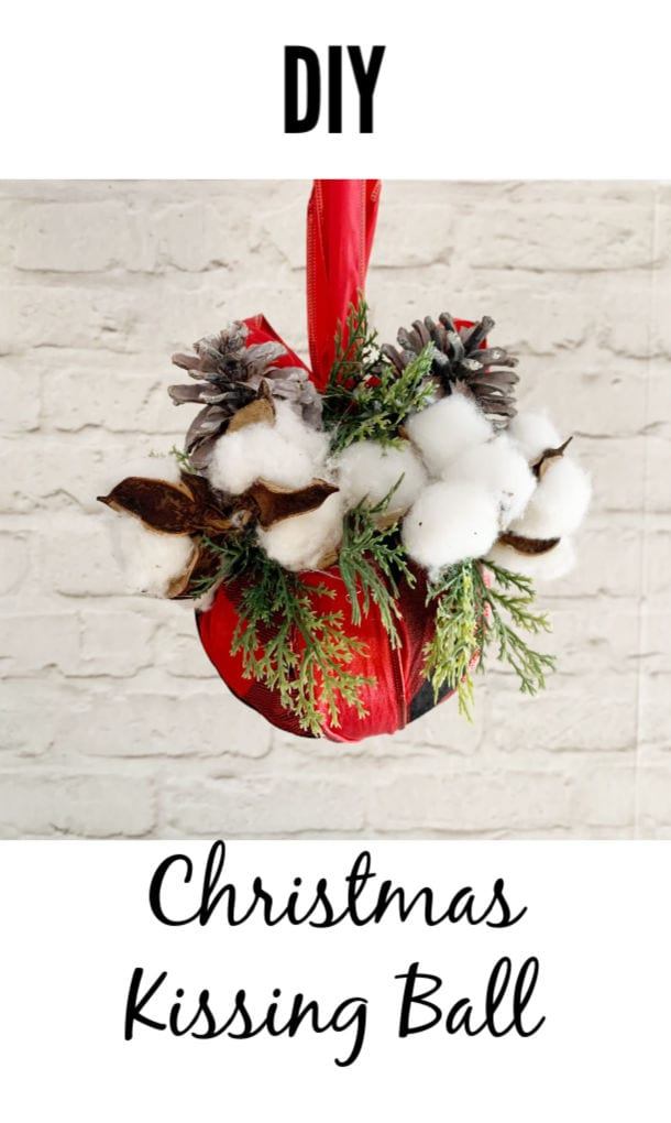 You're going to love this project! Get our FREE tutorial and learn how to make a kissing ball from a red buffalo check scarf, pine cones, and faux holiday greenery cover a Styrofoam ball. Super easy and fun to make, too. #DIY #ChristmasDecor via @jugglingactmama