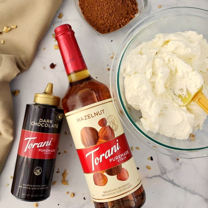 A bottle of Torani Puremade Dark Chocolate Sauce and Torani Puremade Hazelnut Syrup next to a bowl of whipped cream and another of cocoa powder.